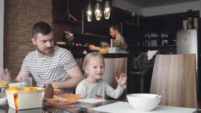 Gay-Eltern-sprechen-mit-kleinen-Tochter-auf-Frühstück