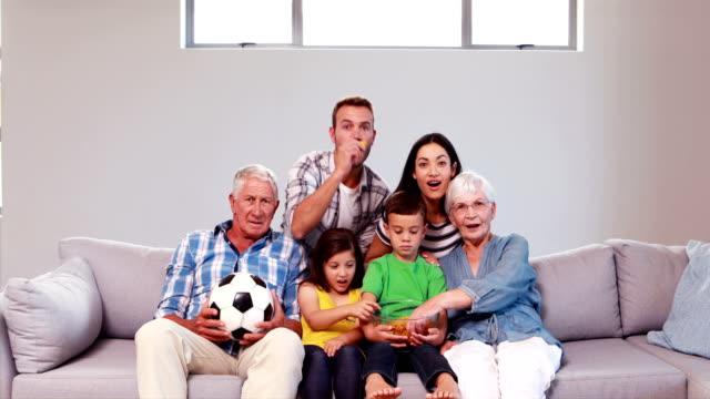 Multi-generation-family-celebrating-goal
