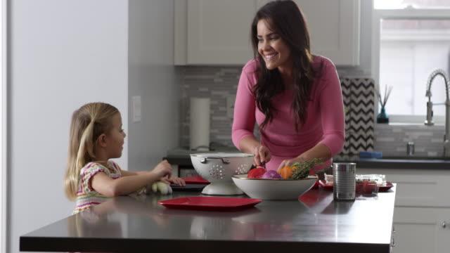 Niña-y-madre-hablando-de-como-se-prepara-una-comida-en-la-cocina-tiro-de-R3D