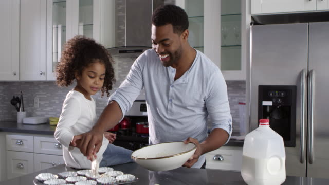 Black-dad-and-young-daughter-prepare-cakes-for-baking-shot-on-R3D