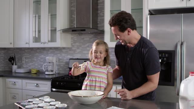 Kaukasische-Mädchen-und-Papa-viel-Spaß-beim-Vorbereiten-Kuchen-Mix-Mischung-Schüsse-aufs-R3D