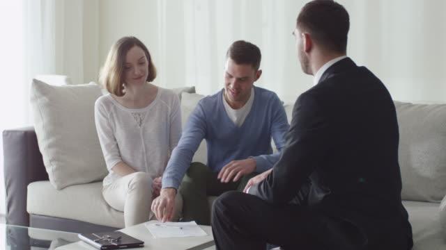 Familia-feliz-firma-contrato-con-el-agente-de-bienes-raíces-