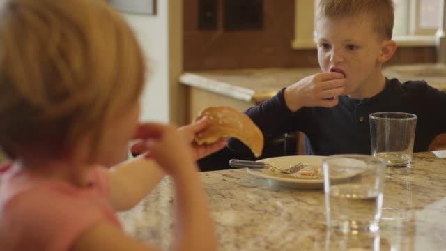 Hermano-y-hermana-compartir-panqueques-y-comer-con-las-manos