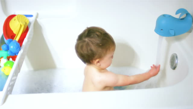 Adorable-little-boy-sits-in-the-bathtub-as-the-water-fills-up-and-he-dries-drinking-the-water