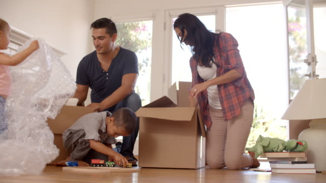 Family-Unpacking-Boxes-In-New-Home-On-Moving-Day