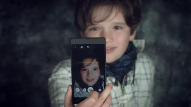 4K-Hi-Tech-Shot-of-a-Child-Making-a-Selfie-on-his-Smartphone