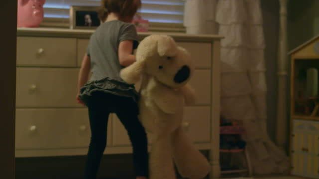 Sad-young-girl-walks-into-her-bedroom-holding-a-stuffed-animal-and-sits-on-the-floor