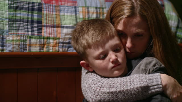 A-mother-with-her-arms-around-her-young-son-whispers-to-him-who-looks-sad