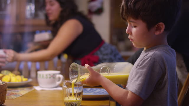 A-boy-pouring-orange-juice-from-a-pitcher-into-a-glass-at-the-table