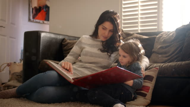 Mother-And-Daughter-At-Home-Looking-Through-Photo-Album