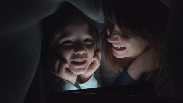 4-k-tiro-de-niño-y-mamá-mirando-la-tableta-debajo-de-la-manta