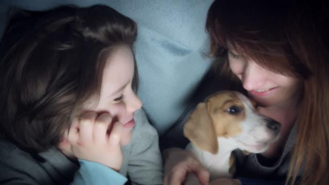 4k-Shot-of-Child-Mom-and-Puppy-Having-Fun-under-Blanket