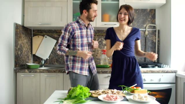 Feliz-hermosa-pareja-bailando-y-besándose-mientras-cocina-en-la-cocina-en-casa