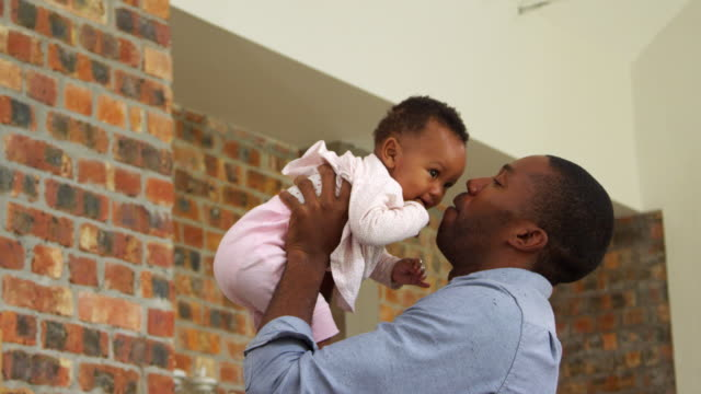 Father-Plays-Baby-Daughter-At-Home-As-Mother-Watches