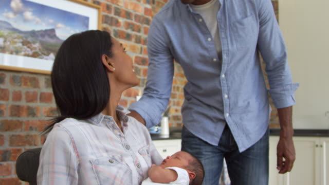 Madre-trabajando-en-ordenador-portátil-tiene-a-un-hijo-recién-nacido-con-el-padre