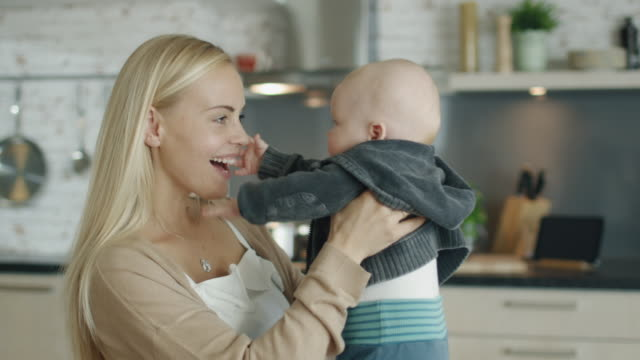 Young-Mother-Holds-and-Plays-with-Her-Baby-while-Standing-on-the-Kitchen