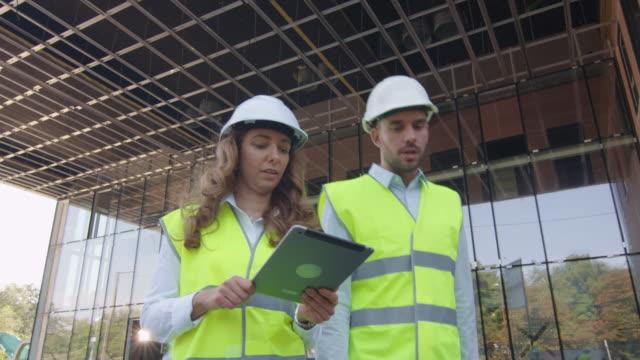 Equipo-de-dos-ingenieros-caminando-hablando-y-usando-Tablet-Computer-Edificio-de-cristal-o-rascacielos-en-construcción-en-segundo-plano-