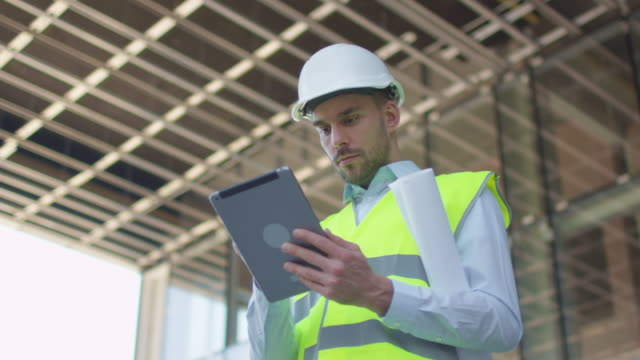 Ingeniero-masculino-usando-Tablet-Computer-Edificio-de-cristal-o-rascacielos-en-construcción-en-segundo-plano-