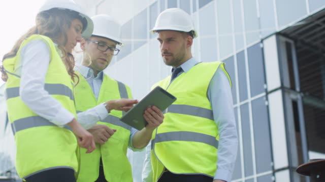 Equipo-de-tres-ingenieros-que-tienen-la-conversación-y-el-uso-de-Tablet-Computer-Edificio-de-cristal-en-construcción-en-el-fondo-