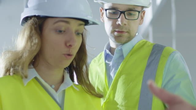 Team-of-Engineers-in-Hard-Hats-Having-Conversation-Looking-at-Blueprint-inside-Building-Under-Construction-