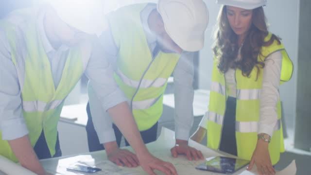 El-equipo-de-ingenieros-se-inclina-sobre-el-plano-grande-y-la-conversación-dentro-del-edificio-en-construcción-