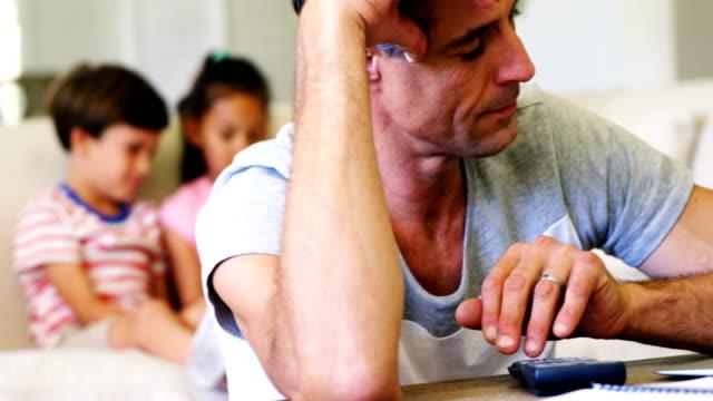 Tense-man-using-calculator-in-living-room
