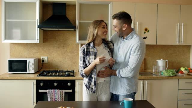 Attraktives-Mädchen-zeigt-Schwangerschaftstest-Ergebnis-zu-ihrem-Freund-und-Surpise-ihn-in-der-Küche