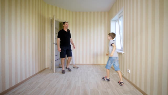 Happy-family-walking-in-new-house-Joyful-boy-opening-door-entering-his-room-for-the-first-time-Mother-father-and-son-standing-inside-of-their-modern-apartment-discussing-future-interior