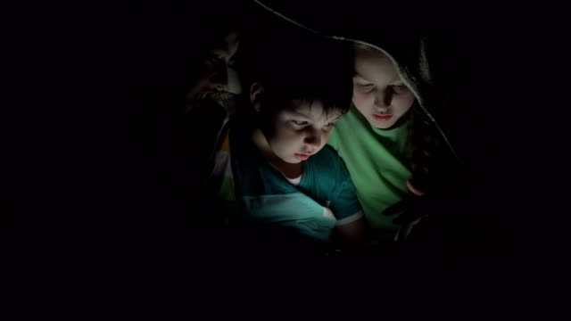 Kids-playing-in-the-tablet-under-the-covers