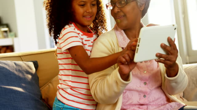 Smiling-grandmother-and-granddaughter-using-digital-tablet-on-sofa-in-living-room-4k
