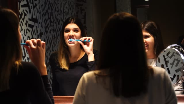 Teenager-Dancing-and-Singing-while-Brushing-Teeth-at-Mirror