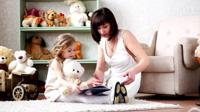 Madre-e-hija-leyendo-un-libro-jugar-diversión-abrazos-juntos-4k