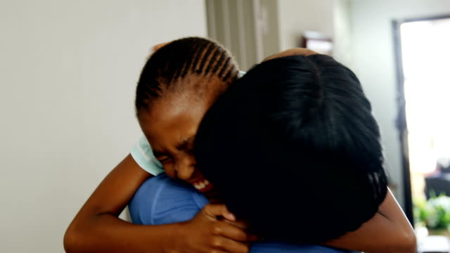 Mother-and-daughter-embracing-each-other-in-living-room-4k