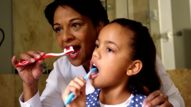 Grandmother-and-granddaughter-brushing-together-in-bathroom-4k