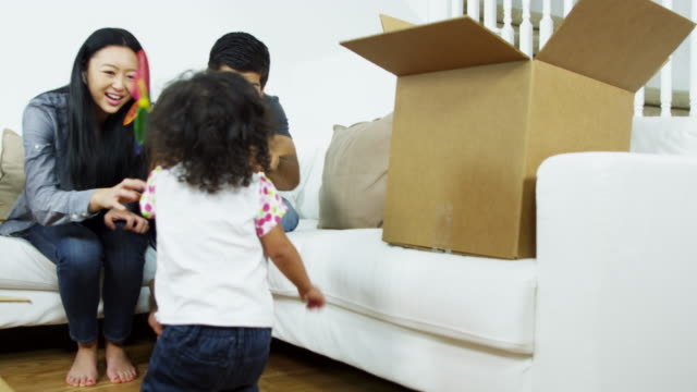 Padres-étnicos-jugar-a-muchacha-infantil-en-nueva-casa