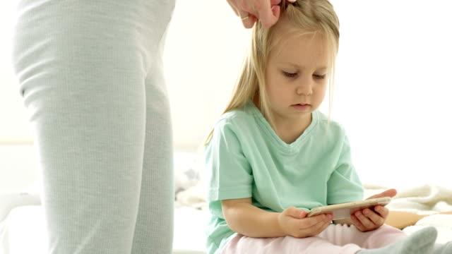 Madre-poner-pelo-de-hijas-en-coletas-Una-familia-feliz-Día-de-las-madres-Día-de-la-mujer