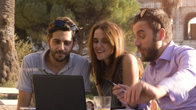 Three-young-people-working-together-on-a-project-with-laptop-and-tablet-brainstorming-writing-talking-and-researching-sitting-at-bar-restaurant-table-in-front-of-colosseum-in-rome-at-sunset