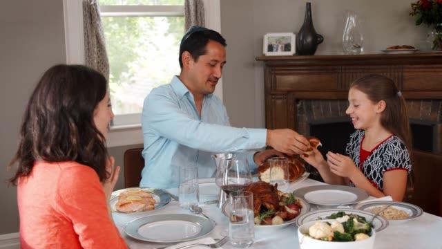 Jewish-man-sharing-challah-bread-with-family-at-Shabbat-meal
