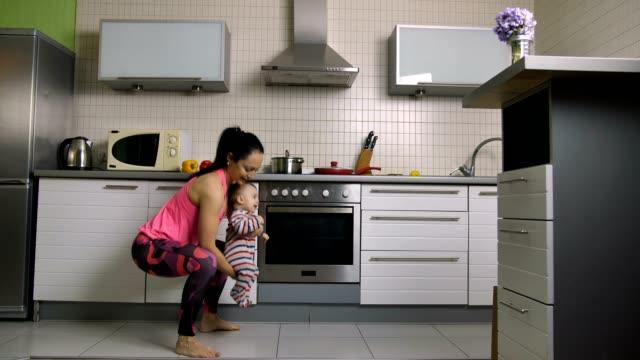 Mujer-sonriente-haciendo-estocadas-con-hijo-en-las-manos