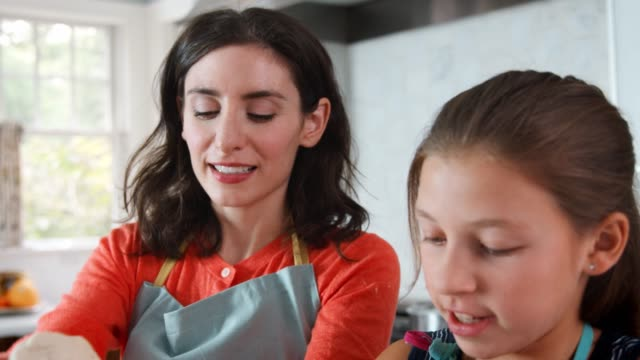 Girl-and-mother-preparing-dough-for-challah-bread-close-up