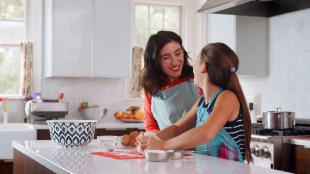 Jewish-daughter-enjoys-kneading-challah-dough-with-mother
