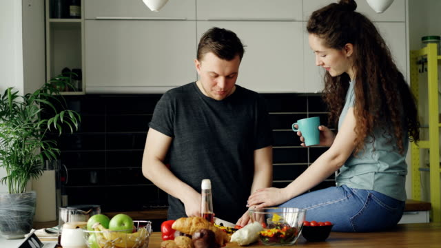 Happy-young-couple-cooking-and-chatting-happily-while-man-cutting-vegetables-for-breakfast-in-the-kitchen-at-home-Relationship-and-family-concept