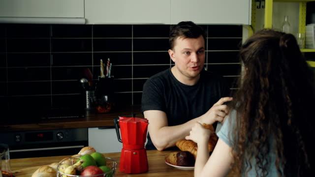 junge-caucasian-Paar-sitzt-am-Tisch-in-modernen-Küche-zu-Hause-weitertanzen-etwas-geschweiften-Frau-sitzt-zurück-Kamera-Tee-trinken-und-Essen-Croussant-halten-sie-Tassen