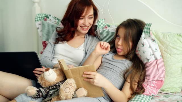 Hijita-linda-con-joven-madre-amorosa-viendo-fotos-graciosas-y-riendo-al-leer-el-cuento-de-hadas-libro-sentados-juntos-en-la-acogedora-cama-en-el-hogar