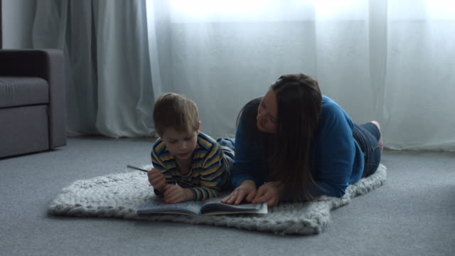 Single-mother-helping-her-cute-son-with-homework