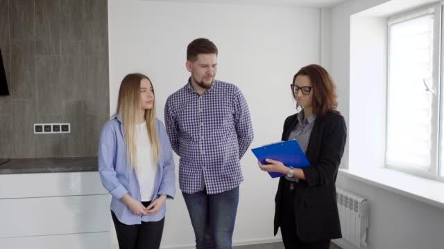 Familia-de-dos-y-agente-inmobiliario-discutir-contrato-interior