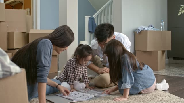 Parents-and-Children-Looking-at-Layout-Plan-of-New-House