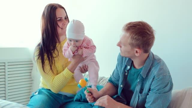 Mamá-tiene-el-bebé-en-sus-brazos-padre-juega-con-el-bebé-Familia-sentado-en-una-cama-en-una-habitación-blanca