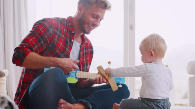 Dad-and-toddler-son-playing-with-instruments-close-up