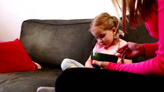 Mom-feeds-a-little-girl-who-can-t-take-her-eyes-off-her-smartphone